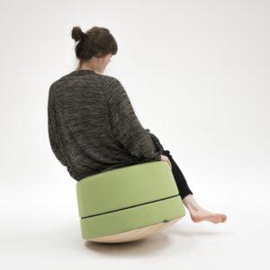 Meisje zit op de BuzziBalance, een voet van de vloer. Een ergonomische manier van zitten en relaxen.