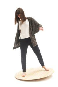 Meisje houdt zich staande op houten BuzziBalance schommelschaal. Een goede evenwichtsoefening en actieve ontspanning.